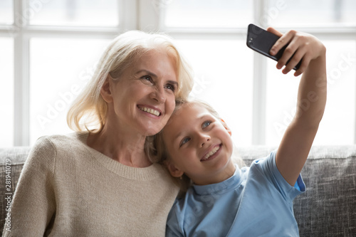 Foto auf Leinwand Texturen Cheerful grandmother and little granddaughter using phone taking selfie
