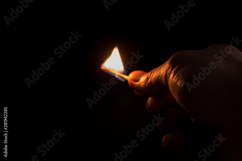 Leinwand Poster  burning match on a dark background, male hand in blackout