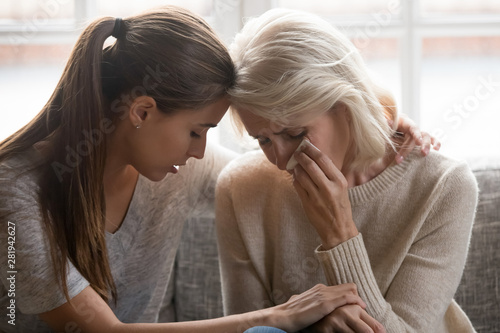 Foto Grownup daughter soothe aged mother holds her hand feeling empathy