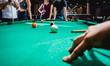 Leinwandbild Motiv Young man trying to hit the ball in billiard.