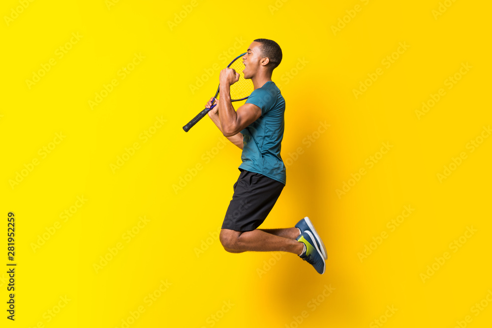 Fototapeta Afro American tennis player man over isolated yellow background