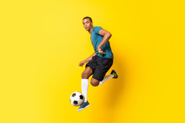 Afro American football player man over isolated yellow background