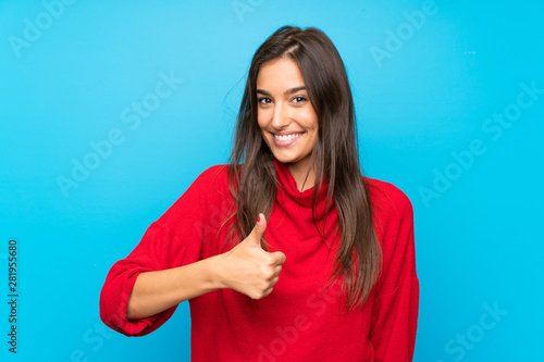 Young woman with red sweater over isolated blue background giving a thumbs up gesture