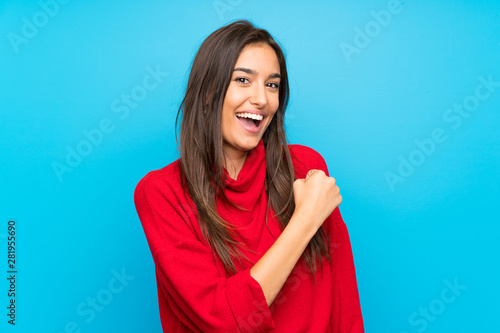 Photo  Young woman with red sweater over isolated blue background celebrating a victory