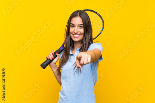 Fotografia  Young tennis player woman over isolated yellow wall points finger at you with a