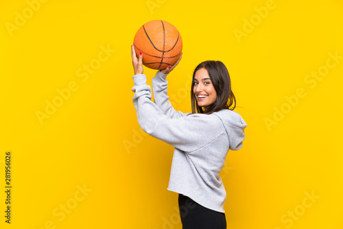 Fotomural  Young woman playing basketball over isolated yellow background