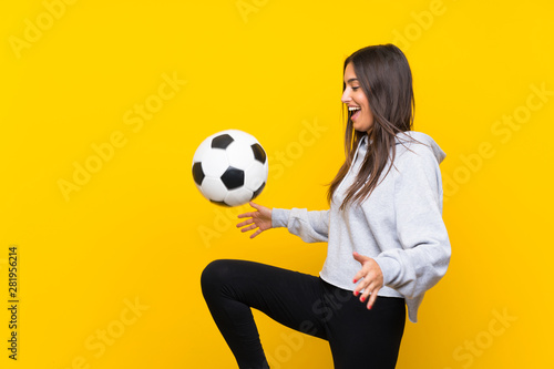 Fotografie, Obraz  Young football player woman over isolated yellow background