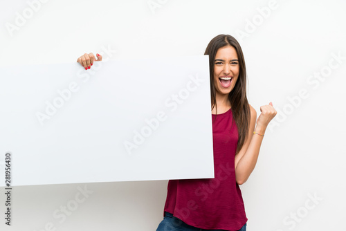 Canvastavla  Young woman over isolated white background holding an empty white placard for in