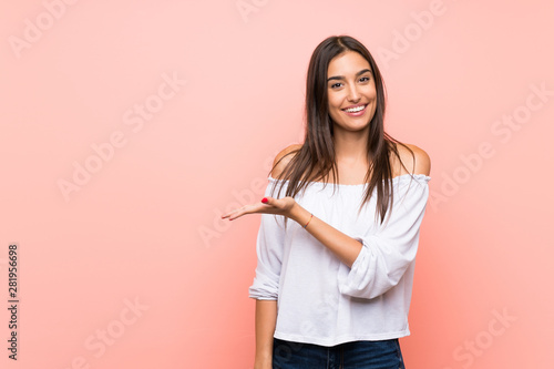 Young woman over isolated pink background presenting an idea while looking smiling towards