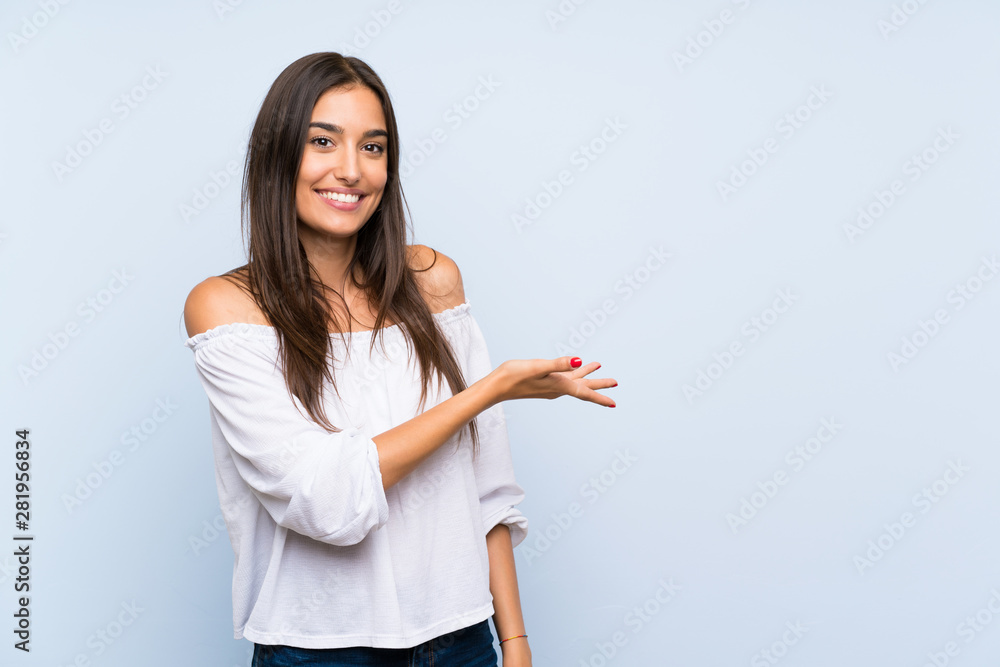 Fototapeta Young woman over isolated blue background extending hands to the side for inviting to come