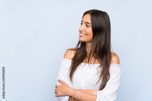 obraz PCV Young woman over isolated blue background looking to the side