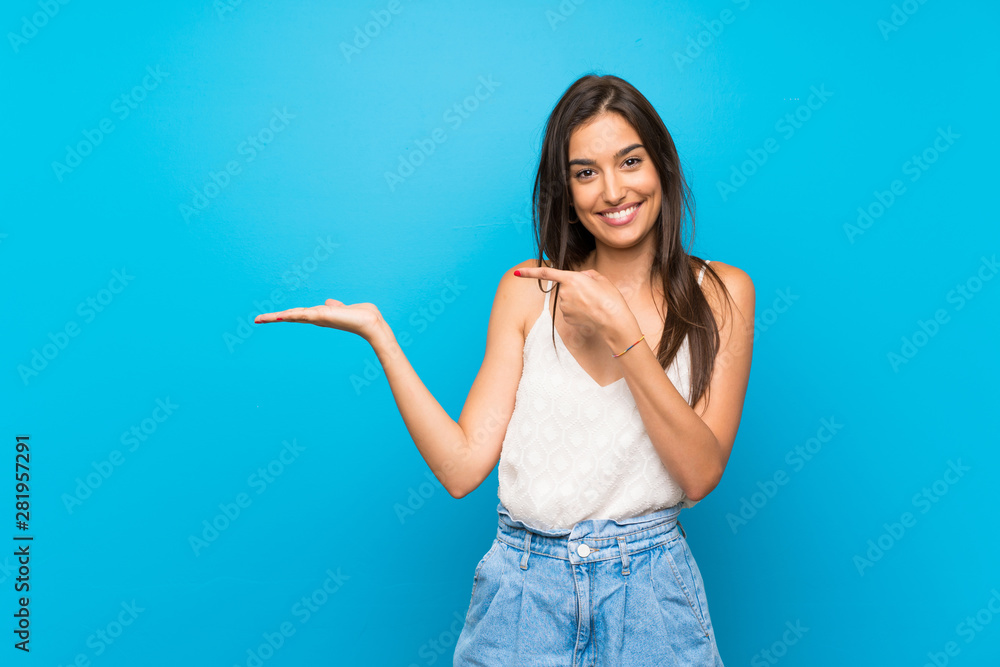 Fototapety, obrazy: Young woman over isolated blue background holding copyspace imaginary on the palm to insert an ad
