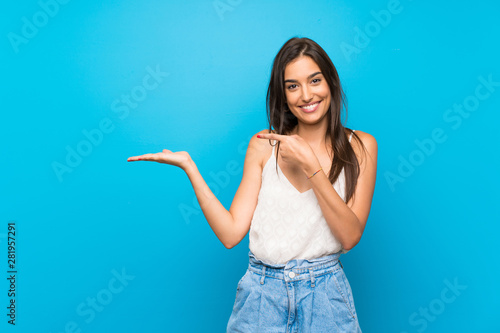 Fotografía  Young woman over isolated blue background holding copyspace imaginary on the pal