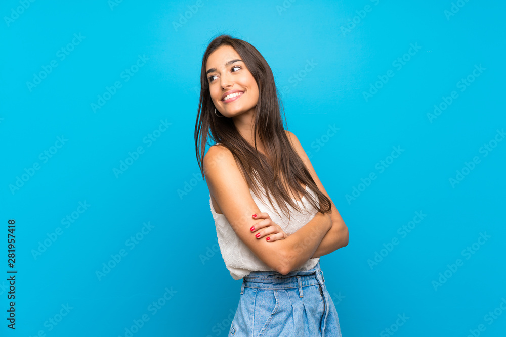Fototapeta Young woman over isolated blue background Looking front