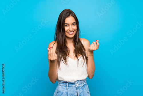 Fototapeta Young woman over isolated blue background making money gesture obraz