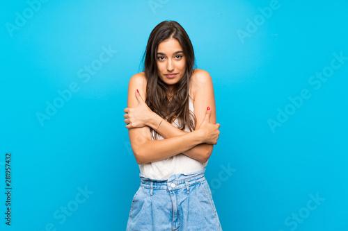 Fototapeta Young woman over isolated blue background freezing