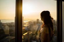 マンションの窓から夕焼けを見る女性