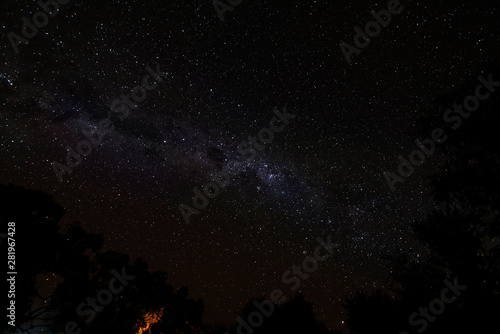 Photo Cloudless starlit night sky with Milky Way and bright stars with firelight and t