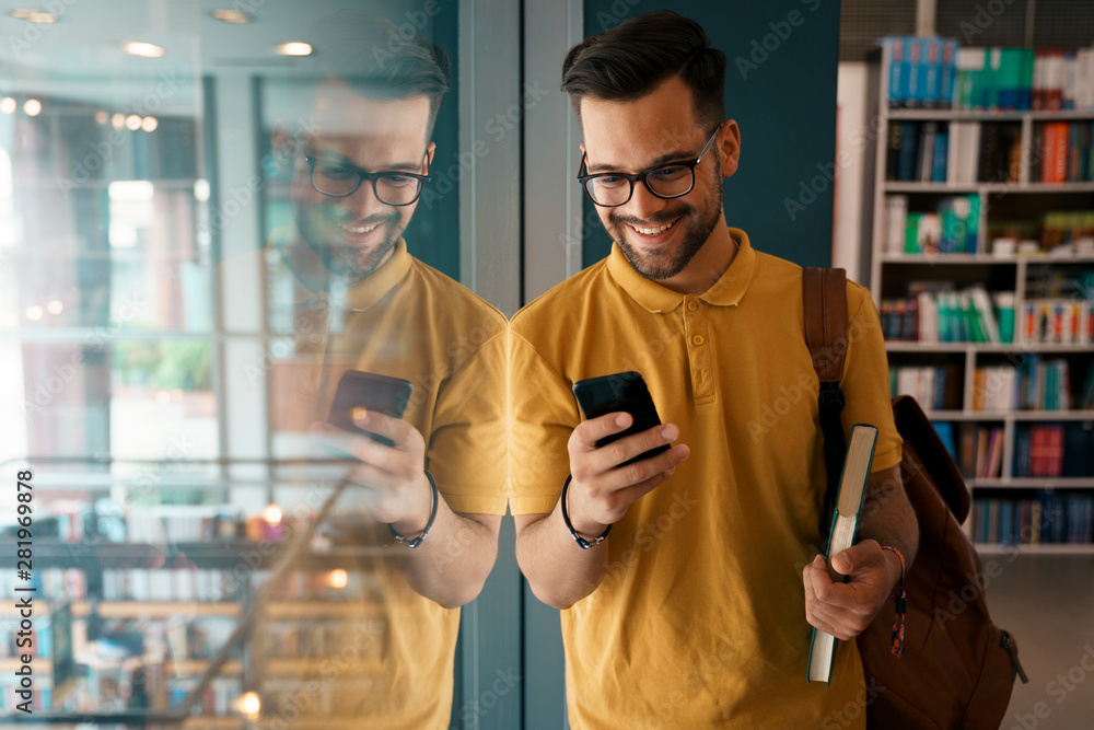 Photo  Young happy college man using mobile phone at the university - Stock Photo