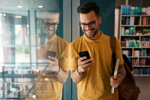 Young happy college man using mobile phone at the university - Stock Photo Wallpaper Mural