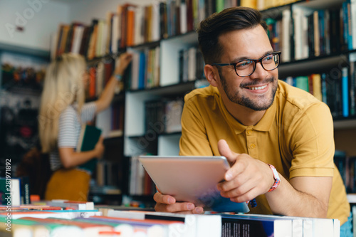 Photo  Young happy college man using digital tablet at the university - Stock Photo