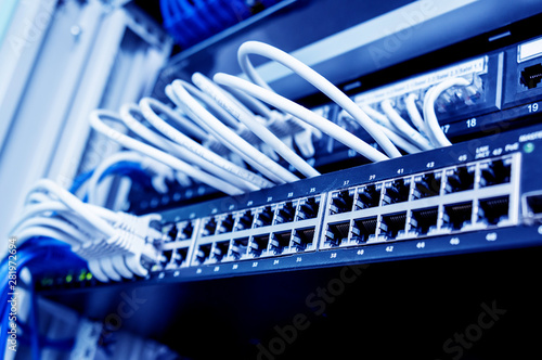 Photo Network switch and ethernet cables in red and white colors