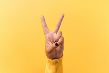 Hand Gesture V Sign For Victory Or Peace Sign Over Yellow Background