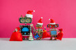canvas print picture - Happy New Year Merry Christmas robots greeting card. Three funny Santa Claus robotic toys with red bags of gifts, Xmas pine tree toy on pink wall background. For robot standing on the right copy space