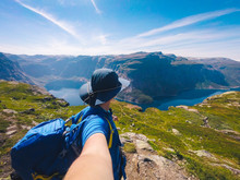Ringedalsvatnet Lake Near Trolltunga. Blue Lake In Norway. Woman Tourist In Hat And Backpack Stands Back And Holds Camera In Hand Takes Selfie Photo On Background Mountains And Lake Nature