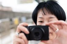 Mature Asian Woman Using Digital Camera
