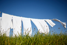 Clean White Clothes Hanging On A Rope Moved By The Wind In Green Meadow