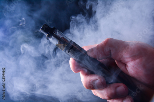 Carta da parati Abstract image of an electronic cigarette in a hand on a background of smoke