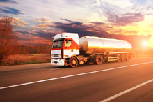 Big Metal Fuel Tanker Truck Shipping Fuel On The Countryside Road In Motion With Forest Against Sky With Sunset