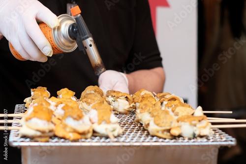 Vászonkép Grilled seafood skewer;  Scallops snd sea urchin eggs  at Tsukiji fish market, Tokyo, Japan