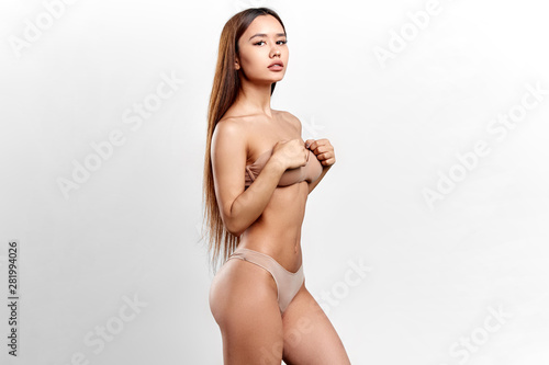 fototapeta na lodówkę slim sexy girl with palms on her breast showing her perfect muscular body. wellness, wellbeing. isolated white background, studio shot