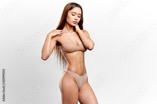 sexy passionate girl with closed eyes touching her neck. looking down, desire, passion concept. isolated white background, studio shot - 281994035
