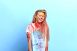 Leinwanddruck Bild - blonde girl with closed eyes laughing at her funny appearance. close up portrait, isolated blue background