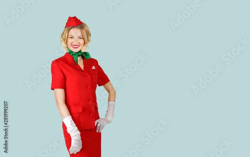 Photo Beautiful stewardess wearing in red uniform on gray background.