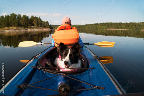 Fotografija The owner and the dog in a life jacket floating in a kayak boat.