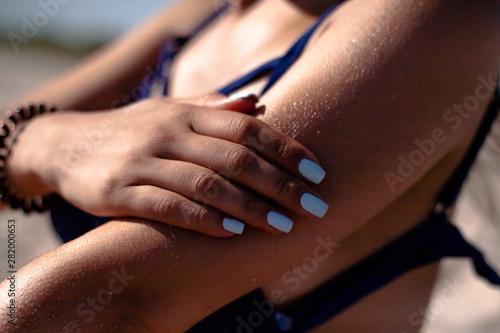 Photo  Girl smears sunblock. On the beach uses tanning oil.
