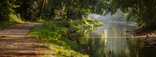 Panorama Tree Lined Walking And Jogging Path On A Calm River Bank With Dappled Morning Light