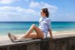 Junge Frau sitzt am Strand auf Mauer in Morro Jable Jandia Fuerteventura