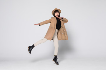 Young pretty girl jumping in beige coat isolated on white background