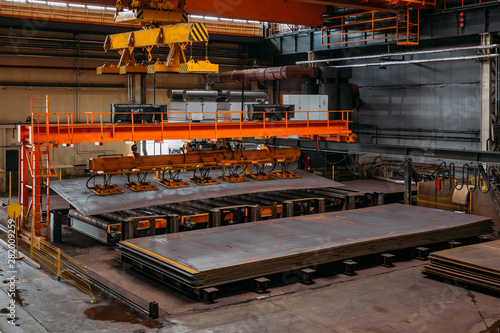 Overhead crane with vacuum handling grippers lifting iron sheets Wallpaper Mural