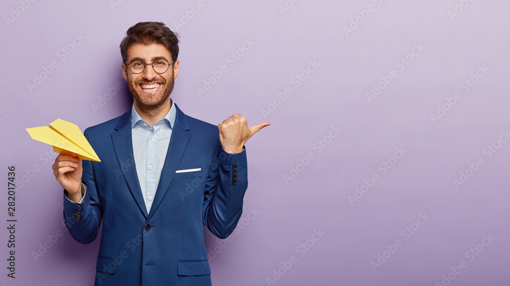 Fototapeta Business success concept. Waist up shot of happy prosperous businessman holds hand made paper airplane, points away with thumb, shows blank space for your promotional content, being in office