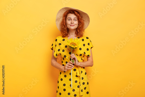 Valokuva  Indoor shot of beautiful smiling red haired woman holds sunflower, enjoys summer time, wears straw hat, stylish dress, poses over yellow background
