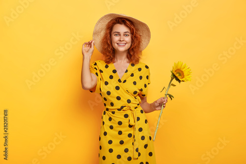 Valokuva  Summer portrait of smiling mirthful ginger lady with tender smile, stands with s