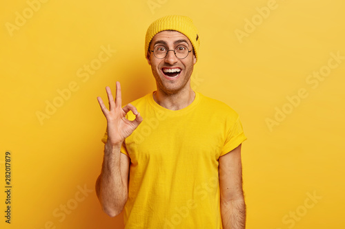 Glad satisfied man shows okay gesture or approval sign, gives positive reply, asserts everything is ok, poses pleased, wears bright vivid clothes, round spectacles, isolated on yellow studio wall Wallpaper Mural