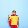 canvas print picture - Shocked bearded ginger man superhero has great courage, dressed in yellow t shirt, red shorts and cloak, points above on free space, shows something incredible and unexpected, feels like leader