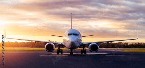 Ingelijste posters Vliegtuig Sunset view of airplane on airport runway under dramatic sky in Hobart,Tasmania, Australia. Aviation technology and world travel concept.
